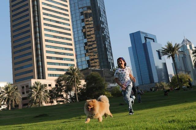 Michelle Rasul chases a friend's dog at a park near her house in Dubai, United Arab Emirates