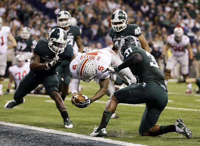 Ohio State's Braxton Miller (5) dives in for a six-yard touchdown run during the second half of a Big Ten Conference championship NCAA college football game against Michigan State, Saturday, Dec. 7, 2013, in Indianapolis. (AP Photo/Michael Conroy)