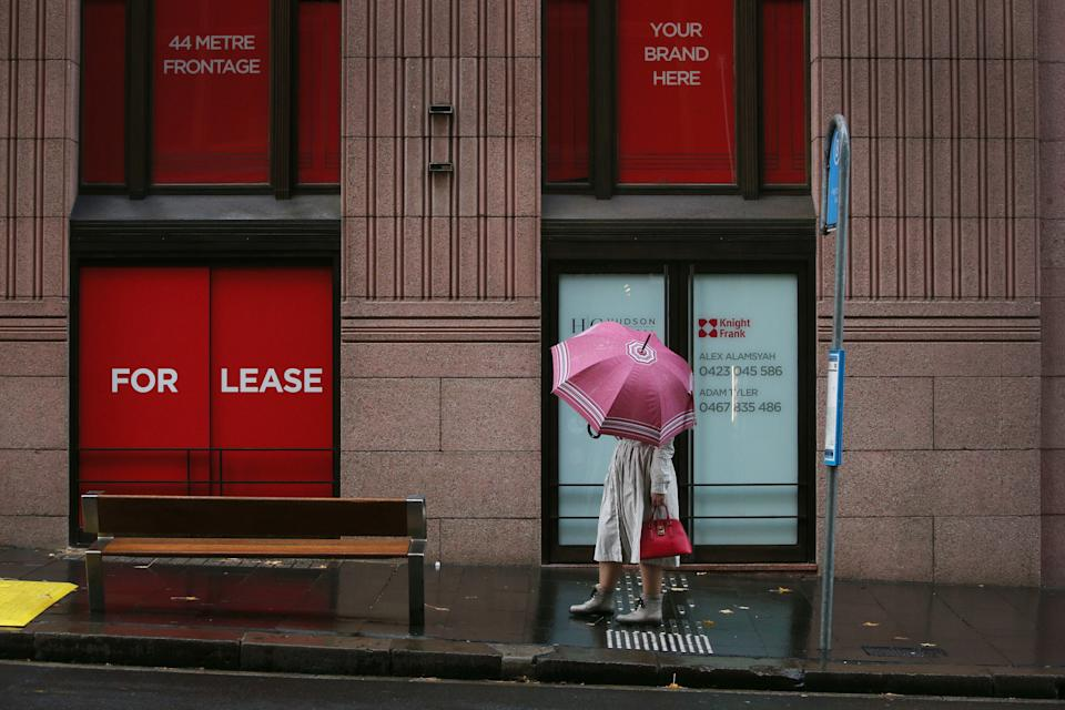 A woman holds an umbrella as she awaits the arrival of a bus in the CBD on June 28, 2021 in Sydney, Australia.