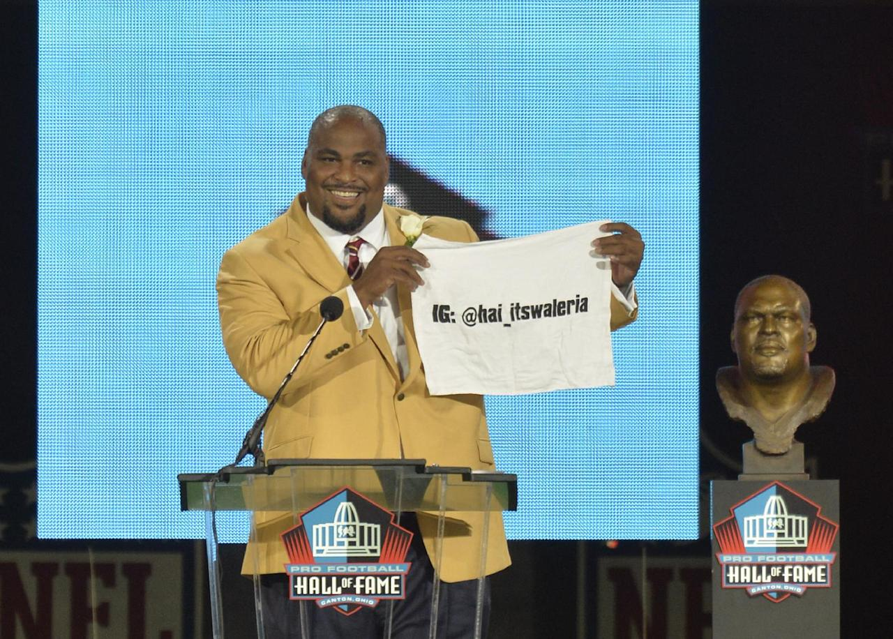 Hall of Fame inductee Walter Jones holds up a towel with his daughter's Instagram address during the Pro Football Hall of Fame enshrinement ceremony Saturday, Aug. 2, 2014, in Canton, Ohio. (AP Photo/David Richard)