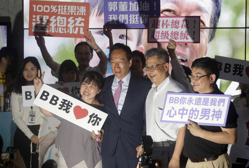 FILE - In this June 21, 2019, file photo, Terry Gou, center, chairman of Foxconn, the world's largest contract assembler of consumer electronics, poses with supporters for a photo after the company's annual shareholders meeting in New Taipei City, Taiwan. Gou has given up on making a bid for Taiwan's presidency. Gou announced his decision in a statement late Monday, Sept. 16, 2019, one day before a deadline to register for the race. (AP Photo/Chiang Ying-ying, File)