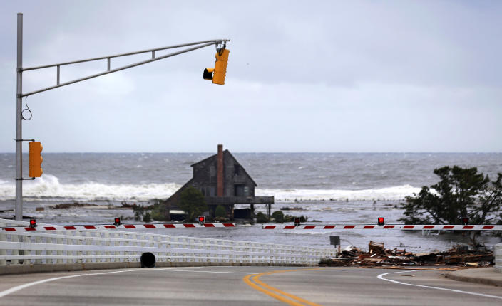 A lone home sits on the beach in an area that residents say was filled with homes but are now gone the morning after superstorm Sandy rolled through, Tuesday, Oct. 30, 2012, in Mantoloking, N.J. Debris from Betty Wagner's home, lower right, rests on top of the Mantoloking Bridge. Sandy, the storm that made landfall Monday, caused multiple fatalities, halted mass transit and cut power to more than 6 million homes and businesses. (AP Photo/Julio Cortez)