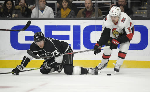 Los Angeles Kings right wing Tyler Toffoli, left, falls as he competes for the puck with Ottawa Senators defenseman Cody Ceci during the second period of an NHL hockey game Thursday, Jan. 10, 2019, in Los Angeles. (AP Photo/Mark J. Terrill)