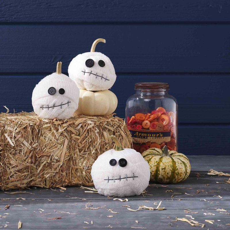 <p>Little ones will get a cackle out of wrapping the mini pumpkins with strips of gauze, but leave the staple gun and hot glue work to a grown-up.</p><p><strong>Make the pumpkin:</strong> Wrap a small white pumpkin with strips of gauze, holding strips in place where necessary with hot-glue. Attach two differently sized black buttons with hot-glue to create eyes. Tack down a length of thin black twine with staple-gun staples to create a mouth.</p>