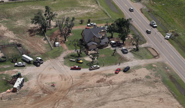 Crews begin to replace electric lines across from a tornado damaged home, Tuesday, May 21, 2019, near Mangum, Okla. Dangerous storms left a string of more than 30 tornadoes across the central U.S., damaging homes in Oklahoma, demolishing a racetrack grandstand in Missouri and inundating the region with water over a short period. (AP Photo/Sue Ogrocki)