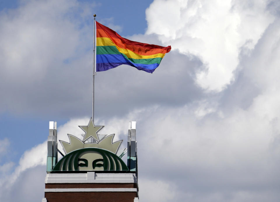 FILE - In this June 24, 2014 file photo, a giant Pride flag flies atop the Starbucks headquarters in celebration of Gay Pride Week in Seattle. More than 400 companies, including Starbucks, have signed on to support civil rights legislation for LGBTQ people that is moving through Congress, advocates said Tuesday, April 27, 2021. The Equality Act would amend existing civil rights law to explicitly include sexual orientation and gender identification as protected characteristics. (AP Photo/Elaine Thompson, File)