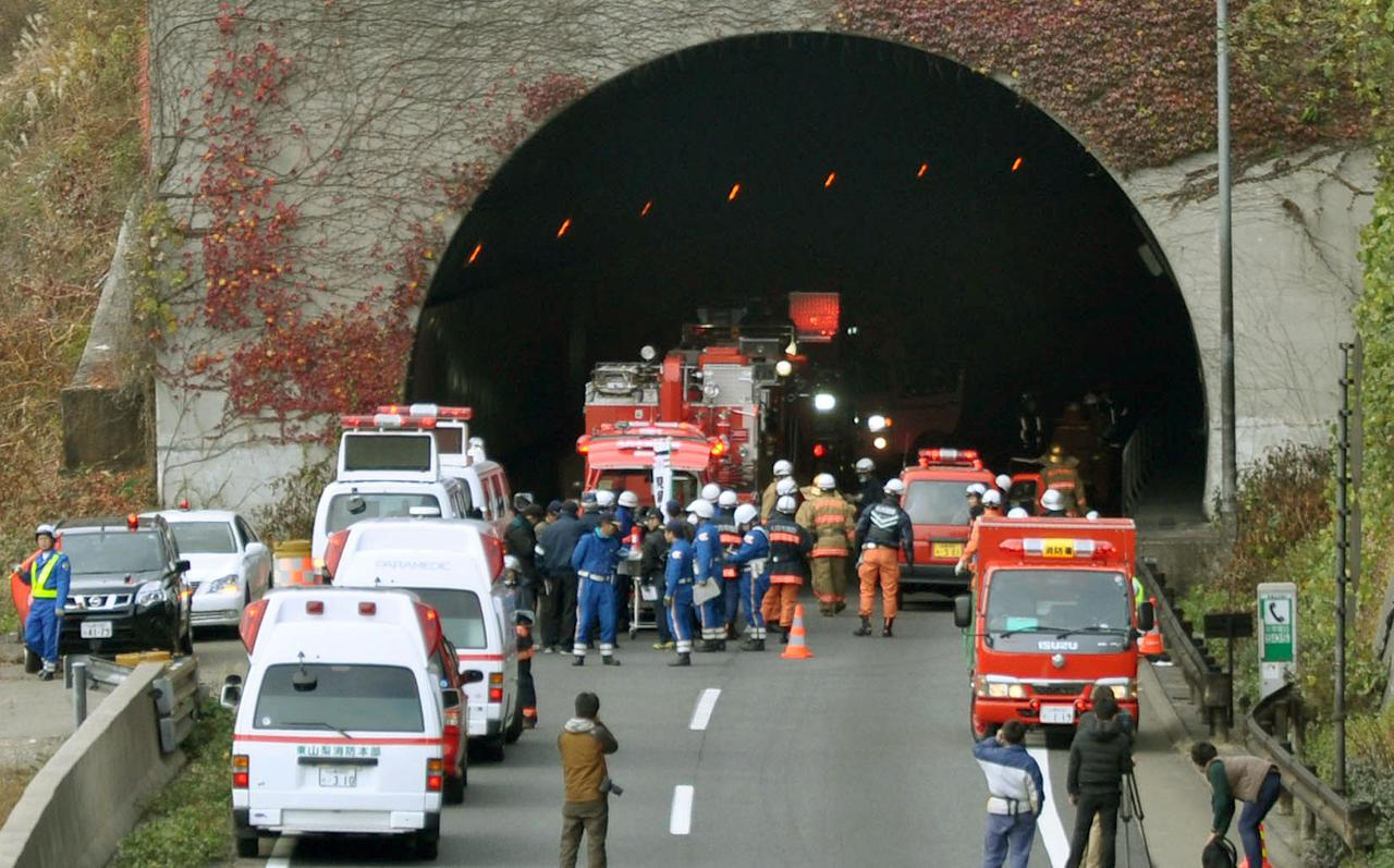 Police officers and firefighters gather at the exit of the Sasago Tunnel on the Chuo Expressway in Otsuki, Yamanashi Prefecture, central Japan, Sunday morning, Dec. 2, 2012. Police said that parts of the tunnel collapsed Sunday morning, trapping an unknown number of vehicles as smoke from a fire inside prevented rescuers from approaching. (AP Photo/Kyodo News) JAPAN OUT, MANDATORY CREDIT, NO LICENSING IN CHINA, FRANCE, HONG KONG, JAPAN AND SOUTH KOREA