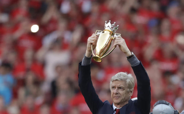 Arsenal's French manager Arsene Wenger holds a trophy he was presented with after the match between Arsenal and Burnley at the Emirates Stadium in London, Sunday, May 6, 2018. The match is Arsenal manager Arsene Wenger's last home game in charge after announcing in April he will stand down as Arsenal coach at the end of the season after nearly 22 years at the helm. (AP Photo/Matt Dunham)