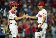 Philadelphia Phillies relief pitcher Ranger Suarez, right, celebrates the win with catcher J.T. Realmuto, left, following the ninth inning of a baseball game against the Atlanta Braves, Friday, July 23, 2021, in Philadelphia. The Phillies won 5-1. (AP Photo/Chris Szagola)
