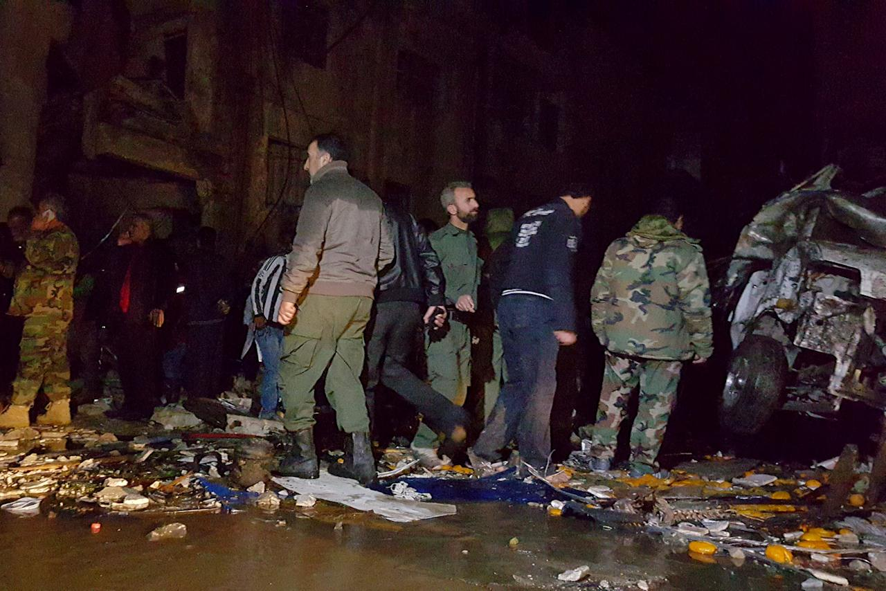 Syrian army soldiers and civilians inspect the site of multiple bomb blasts that hit the Sayeda Zeinab area, a southern district of Damascus, Syria, February 21, 2016. REUTERS/Stringer EDITORIAL USE ONLY. NO RESALE. NO ARCHIVE