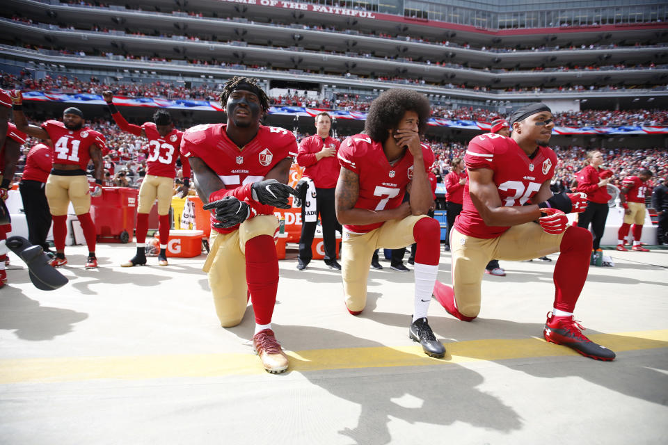 SANTA CLARA, CA - OCTOBER 2: Antoine Bethea #41 and Rashard Robinson #33  of the San Francisco 49ers raise their first during the anthem as Eli Harold #58 while teammates Colin Kaepernick #7 and Eric Reid #35 take a knee, prior to the game against the Dallas Cowboys at Levi Stadium on October 2, 2016 in Santa Clara, California. The Cowboys defeated the 49ers 24-17. (Photo by Michael Zagaris/San Francisco 49ers/Getty Images)