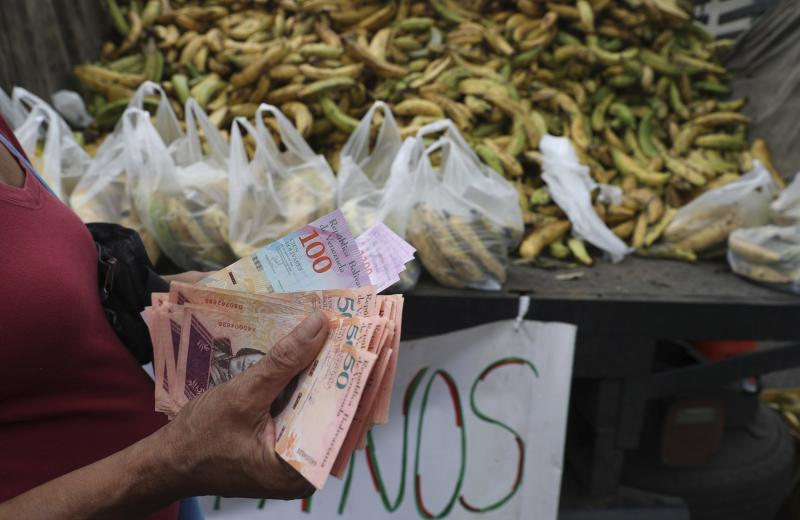 In this May 8, 2019 photo, a woman counts 5,000 Bolivars, almost one dollar, to buy a bag of bananas in the Petare area of Caracas, Venezuela. After 16 years of currency controls, the government is allowing its Bolivar to be exchanged on the floating market starting Monday, May 13, starting at 5,200 Bolivars per U.S. dollar. (AP Photo/Martin Mejia)