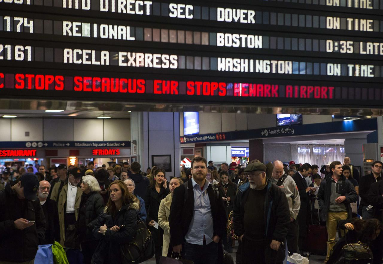 Travelers wait at Pennsylvania Station in New York November 27, 2013. A wintry blast of heavy rain, wind and snow across the eastern United States disrupted Thanksgiving trip plans on Wednesday for some of the millions of people hitting the roads and taking to the skies on the busiest holiday travel day of the year. REUTERS/Eric Thayer (UNITED STATES - Tags: ENVIRONMENT TRANSPORT)