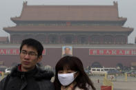 A woman wears a mask as she visits Tiananmen Square in Beijing Sunday, Jan. 13, 2013. People refused to venture outdoors and buildings disappeared into Beijing's murky skyline on Sunday as the capital's air quality went off the index. (AP Photo/Ng Han Guan)