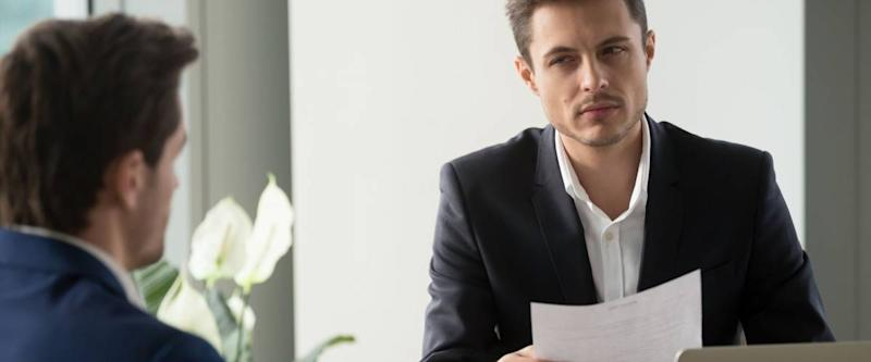Distrustful businessman holding document at meeting, looking at partner with doubt suspicion