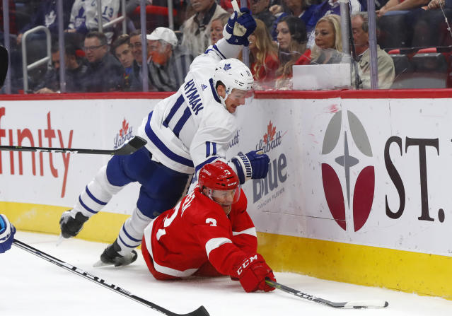 Toronto Maple Leafs center Zach Hyman (11) and Detroit Red Wings defenseman Nick Jensen (3) battle for the puck during the first period of an NHL hockey game Thursday, Oct. 11, 2018, in Detroit. (AP Photo/Paul Sancya)