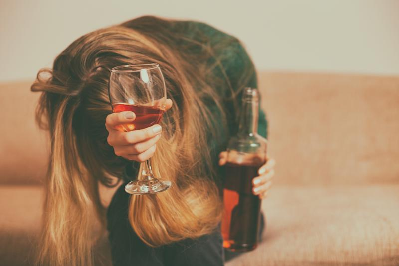 Depressed woman drinking alcohol while sitting alone at sofa.Toned image.