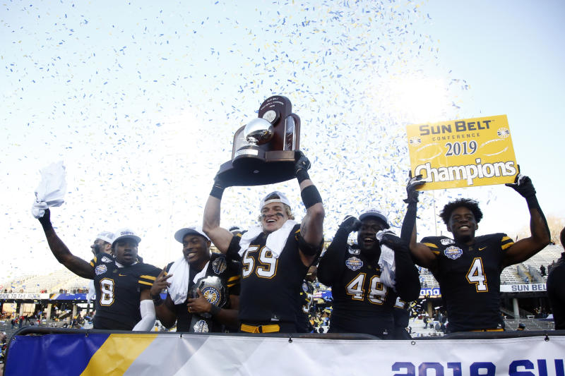 Appalachian State players, from left, defensive back Shemar Jean-Charles (8), running back Darrynton Evans (3), linebacker Jordan Fehr (59), defensive lineman Demetrius Taylor (48) and running back Daetrich Harrington (4) celebrate on stage following their 45-38 win over Louisiana-Lafayette in an NCAA college football game for the Sun Belt Football Championship, Saturday, Dec. 7, 2019, in Boone, N.C. (AP Photo/Brian Blanco)