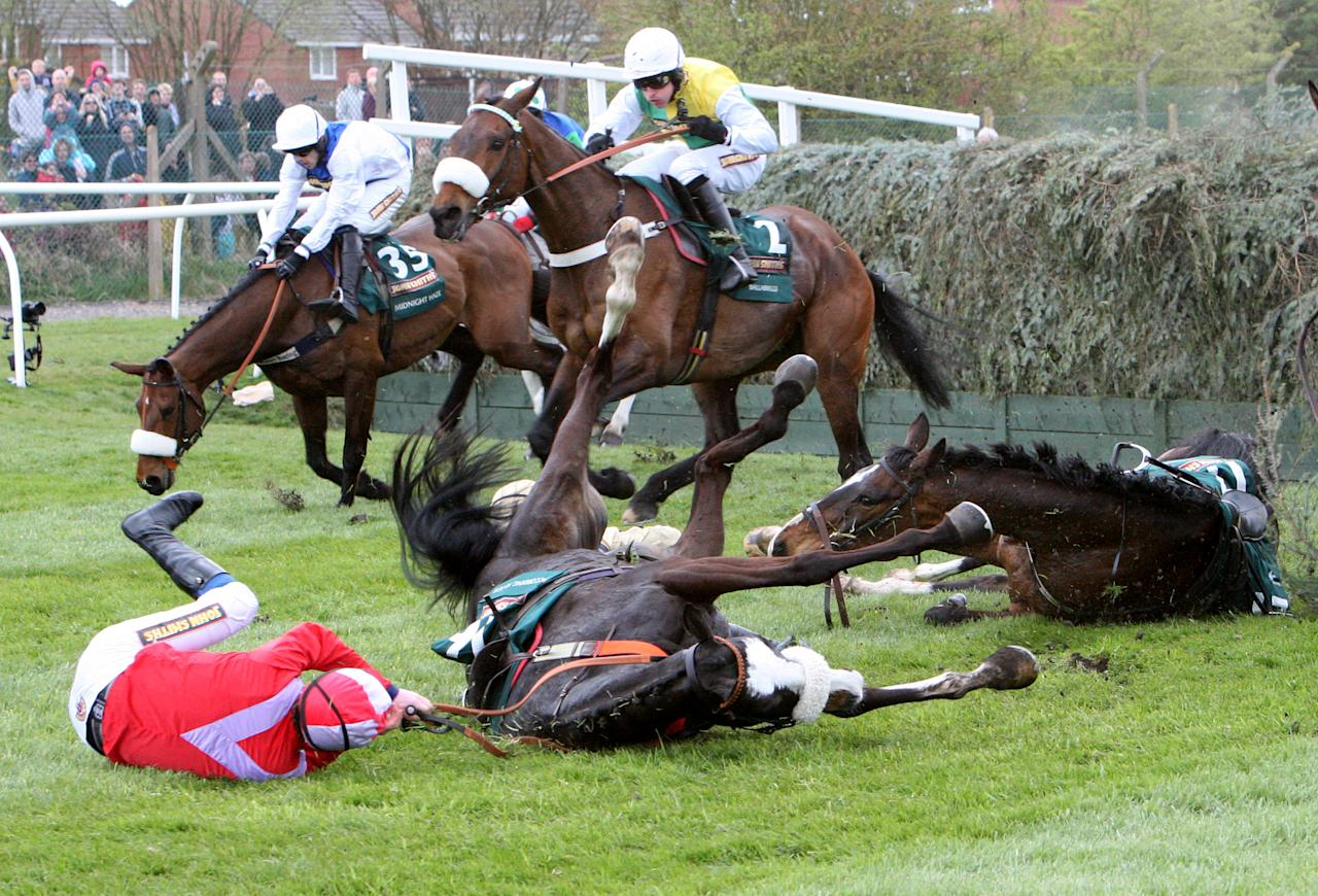 According to Pete ridden by Harry Haynes, left, falls after jumping Becher's Brook during the Grand National at Aintree Racecourse, Liverpool, England, Saturday April 14, 2012. British Grand National favorite Synchronised died Saturday after collapsing during the world's toughest steeplechase, which was won by Neptune Collonges in one of the race's closest finishes.(AP Photo/Scott Heppell)