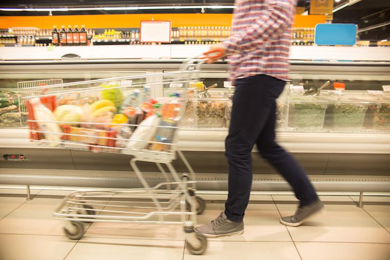 Low section view of unrecognizable man pushing shopping cart in blurred motion while choosing groceries in supermarket