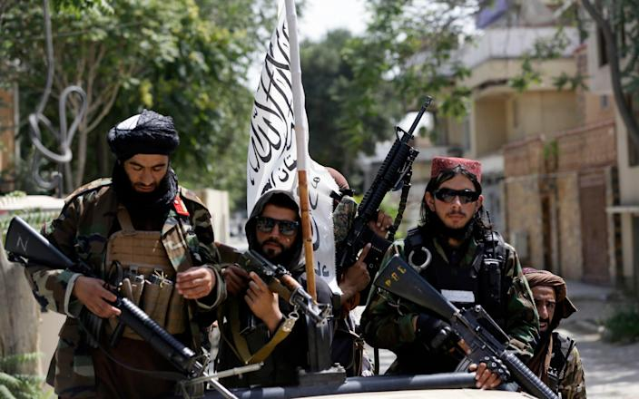 Taliban fighters in Kabul, bearing the country's new flag - AP Photo/Rahmat Gul, File