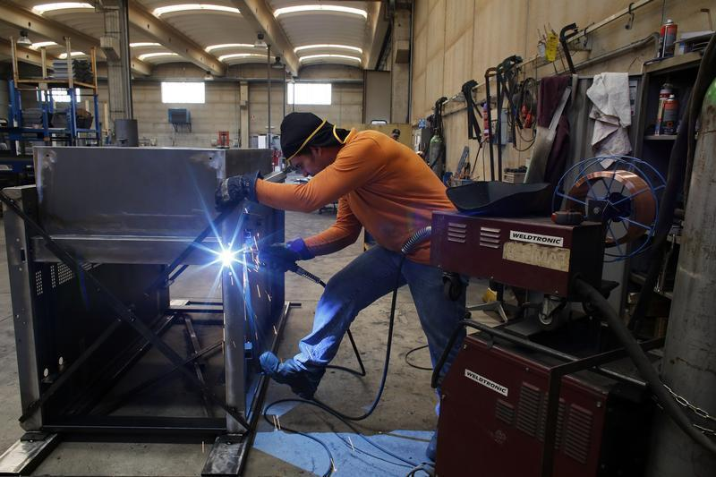 A worker welds a metal furnace in a factory in Gravellona Lomellina