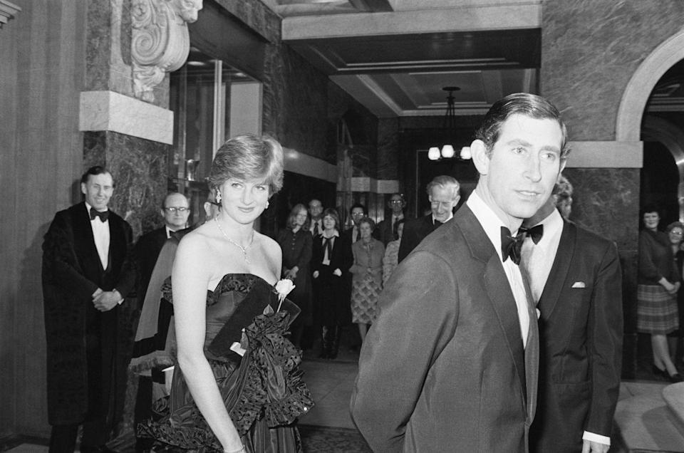 <p>Prince Charles escorts his fiancée on her first royal appearance in March 1981. The couple attended an event at Goldsmiths Hall in London, where Diana wore a strapless taffeta evening gown. </p>