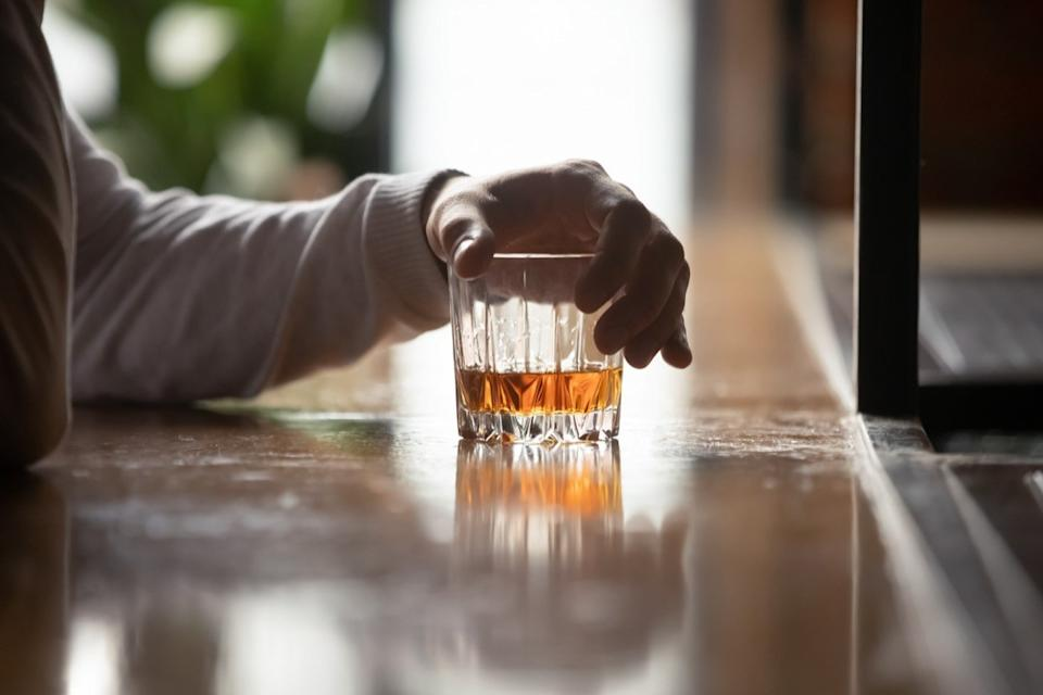 Man's hand holds whiskey glass at bar