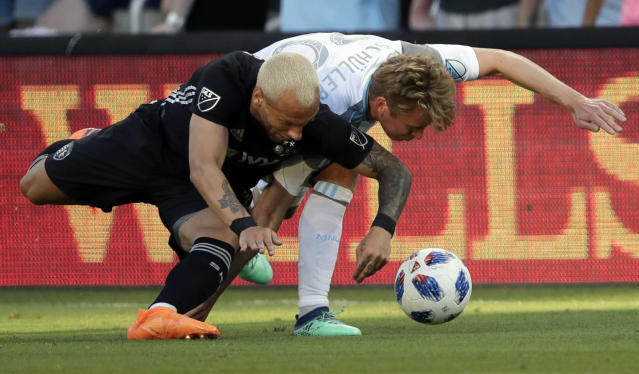 Sporting Kansas City midfielder Yohan Croizet, left, and Minnesota United midfielder Rasmus Schuller (20) struggle for the ball during the first half of an MLS soccer match in Kansas City, Kan., Sunday, June 3, 2018. (AP Photo/Orlin Wagner)
