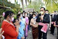 """In this photo released by Government Spokesman Office, Thailand's Prime Minister Prayuth Chan-ocha right, gives the traditional greeting or """"wai"""" in Samut Songkhram province, Thailand, Wednesday, Dec. 2, 2020. Thailand's highest court is set to rule Wednesday, on whether Prayuth has breached ethics clauses in the country's constitution and should be ousted from his position. (Government Spokesman Office via AP) NO SALE"""
