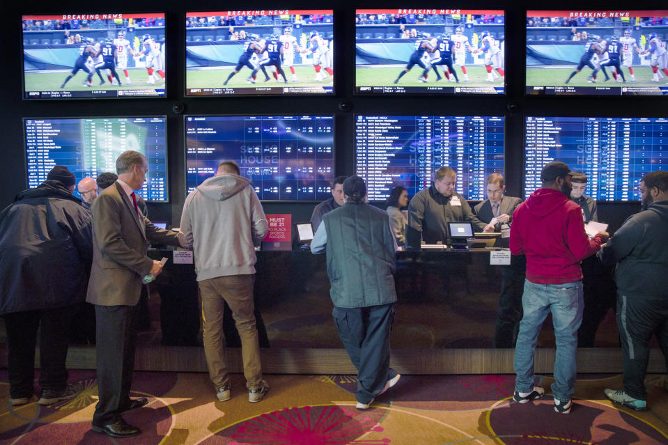 FILE - In this Dec. 13, 2018, file photo, gamblers place bets in the temporary sports betting area at the SugarHouse Casino in Philadelphia. State regulators said Monday, July 19, 2021, that Pennsylvania smashed its record for gambling revenue, reporting nearly $3.9 billion in the last fiscal year as every category of wagering showed growth in one of the nation's largest casino and gambling states. (AP Photo/Matt Rourke, File)