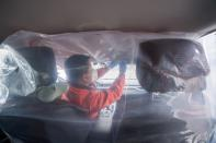 Worker installs plastic film to separate the front seats from the back, inside a vehicle for a car-hailing service as the country is hit by an outbreak of the novel coronavirus, in Taiyuan