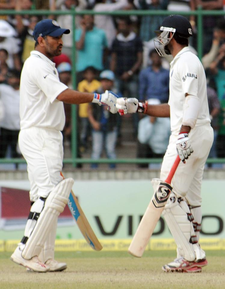 M S Dhoni and Cheteshwar Pujara of India discussing during the 4th test match of Border Gavaskar Trophy, at Ferozeshah Kotla Stadium in Delhi on March 24, 2013. P D Photo by P S Kanwar