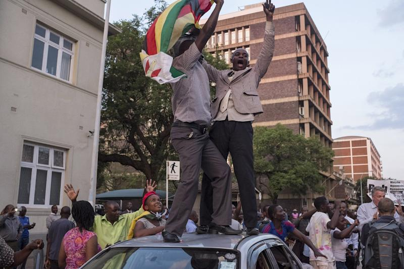 Zimbabweans shout slogans and dance on top of a car.