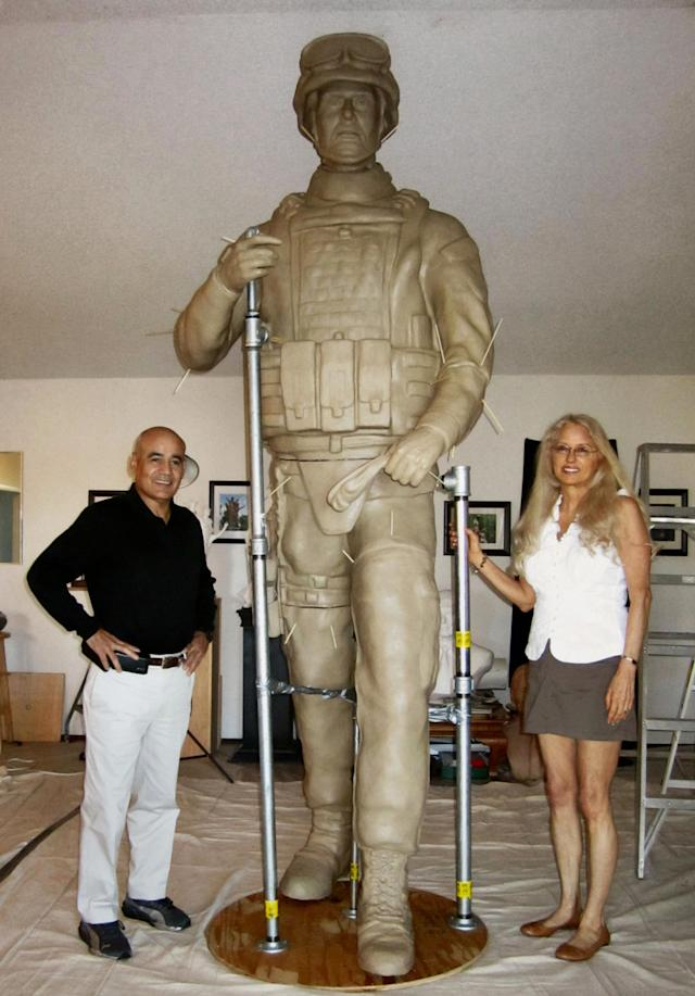 In this Aug. 2, 2012 publicity photo provided by Natural Balance, war handler veteran, author and designer, John Burnam, left, and veteran portrait sculptor, Paula Slater, stand with the silicon bronze 9.5-feet tall military dog handler that is part of the U.S. Working Dogs Teams National Monument shown in the Sculptor's Studio in Hidden Valley Lake, in Calif. (AP Photo/Natural Balance)