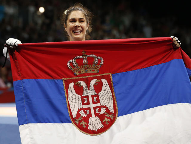 Serbia's Milica Mandic holds a Serbian national flag after defeating France's Anne-Caroline Graffe (not pictured) in their women's 67kg gold medal taekwondo final at the ExCel venue during the London 2012 Olympic Games August 11, 2012. REUTERS/Kim Kyung-Hoon (BRITAIN - Tags: OLYMPICS SPORT TAEKWONDO)
