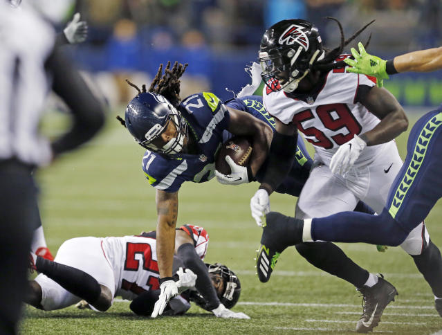Seattle Seahawks' J.D. McKissic (21) tumbles between Atlanta Falcons De'Vondre Campbell (59) and Damontae Kazee on a carry in the first half of an NFL football game, Monday, Nov. 20, 2017, in Seattle. (AP Photo/Stephen Brashear)