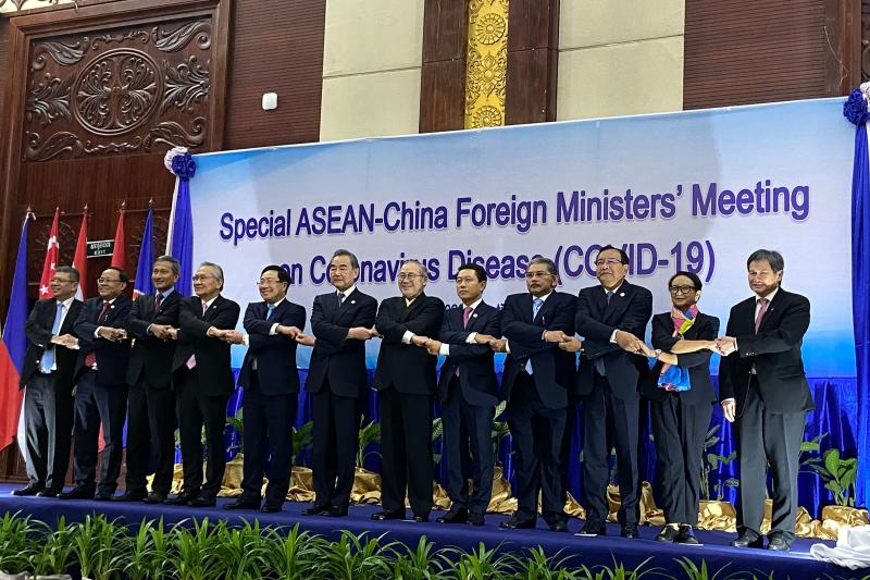 (L-R) Malaysia's Foreign Minister Saifuddin Abdullah, Myanmar's Union Minister for International Cooperation Kyaw Tin, Singapore's Foreign Minister Vivian Balakrishnan, Thailand's Foreign Minister Don Pramudwinai, Vietnam's Foreign Minister Pham Binh Minh, China's Foreign Minister Wang Yi, Philippines' Foreign Minister Teodoro Locsin Jr, Laos' Foreign Minister Saleumxay Kommasith, Brunei's Second Minister of Foreign Affairs Erywan Yusof, Cambodia's Foreign Minister Prak Sokhon, Indonesias Foreign Minister Retno Marsudi, and ASEAN Secretary-General Lim Jock Hoi shake hands on stage at a summit between China and ASEAN (Association of Southeast Asian Nations) on the COVID-19 coronavirus in Vientiane on February 20, 2020. - The deadly coronavirus is set to dominate the agenda of a high-level Vientiane summit February 20, as China's foreign minister meets with his Southeast Asian counterparts whose countries' economies have been hard-hit over fears of widespread contagion. (Photo by Dene-Hern Chen / AFP) (Photo by DENE-HERN CHEN/AFP via Getty Images)