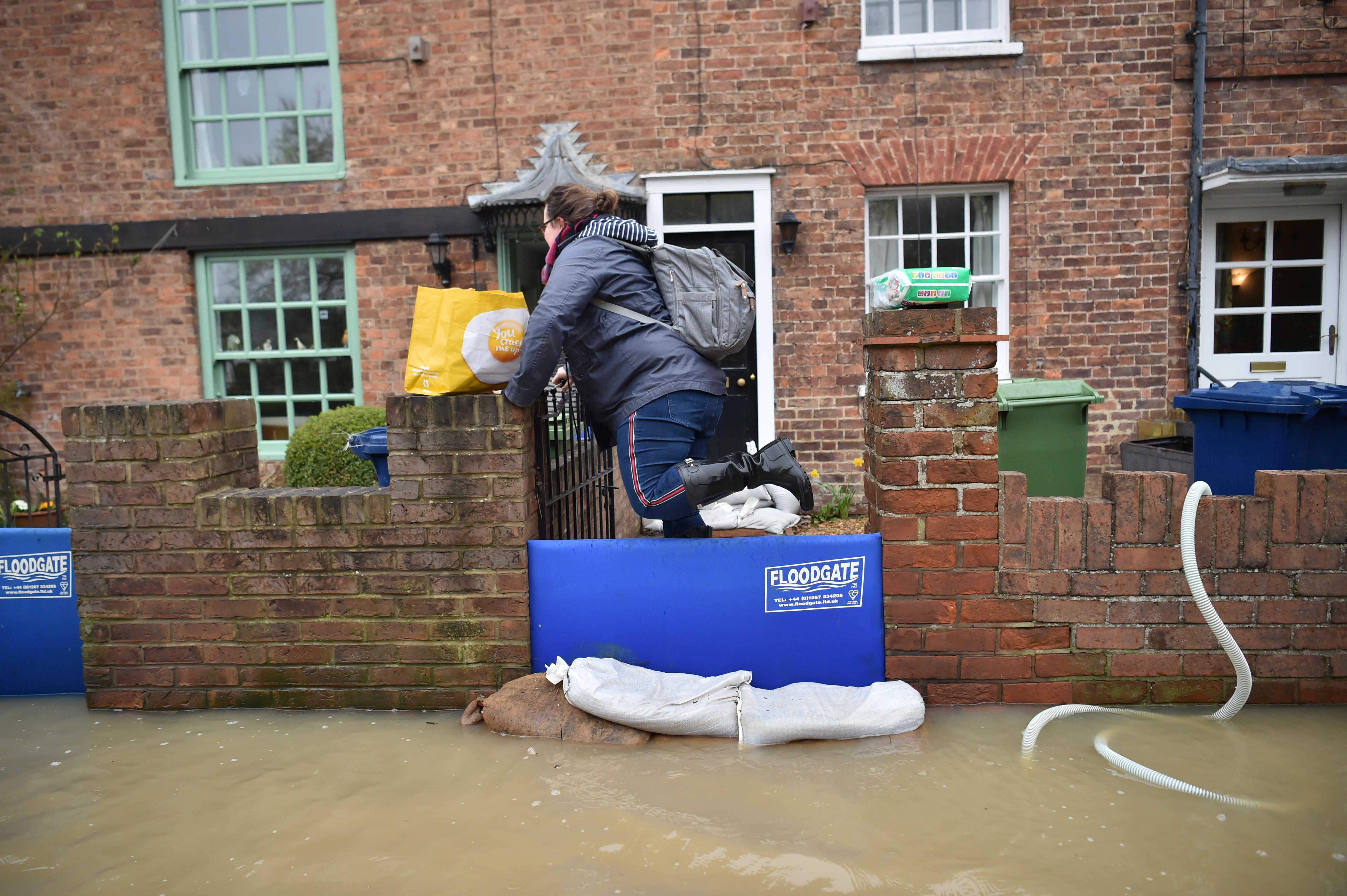 A woman carrying shopping bags through flood water, as pumps and flood barriers help to keep the water from flooding homes in Gloucester Road in Tewkesbury, Gloucestershire, following the aftermath of Storm Dennis.