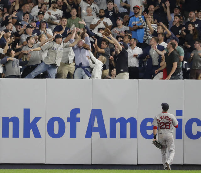 Boston Red Sox's J.D. Martinez (28) watches as fans reach for a home run by New York Yankees' Luke Voit during the fourth inning of a baseball game Wednesday, Sept. 19, 2018, in New York. (AP Photo/Frank Franklin II)