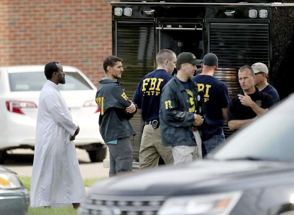 In this Aug. 15, 2017, file photo, law enforcement officials investigate the site of an explosion at the Dar Al-Farooq Islamic Center in Bloomington, Minn. Jury selection is scheduled to begin Monday, Nov. 2, 2020, in the trial of the leader of an Illinois anti-government group who's accused of being the ringleader behind the bombing. (David Joles/Star Tribune via AP File)