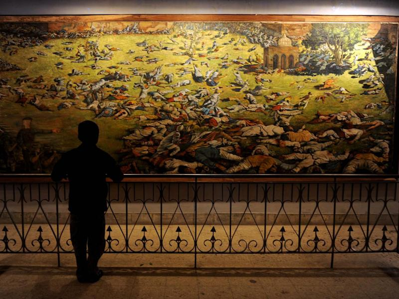 A young visitor looks at a painting depicting the Amritsar Massare at Jallianwala Bagh in Amritsar