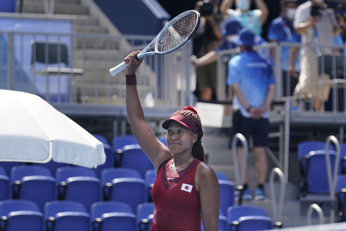 Naomi Osaka, of Japan, waves after winning her match during the first round of the tennis competition at the 2020 Summer Olympics, Sunday, July 25, 2021, in Tokyo, Japan. (AP Photo/Seth Wenig)