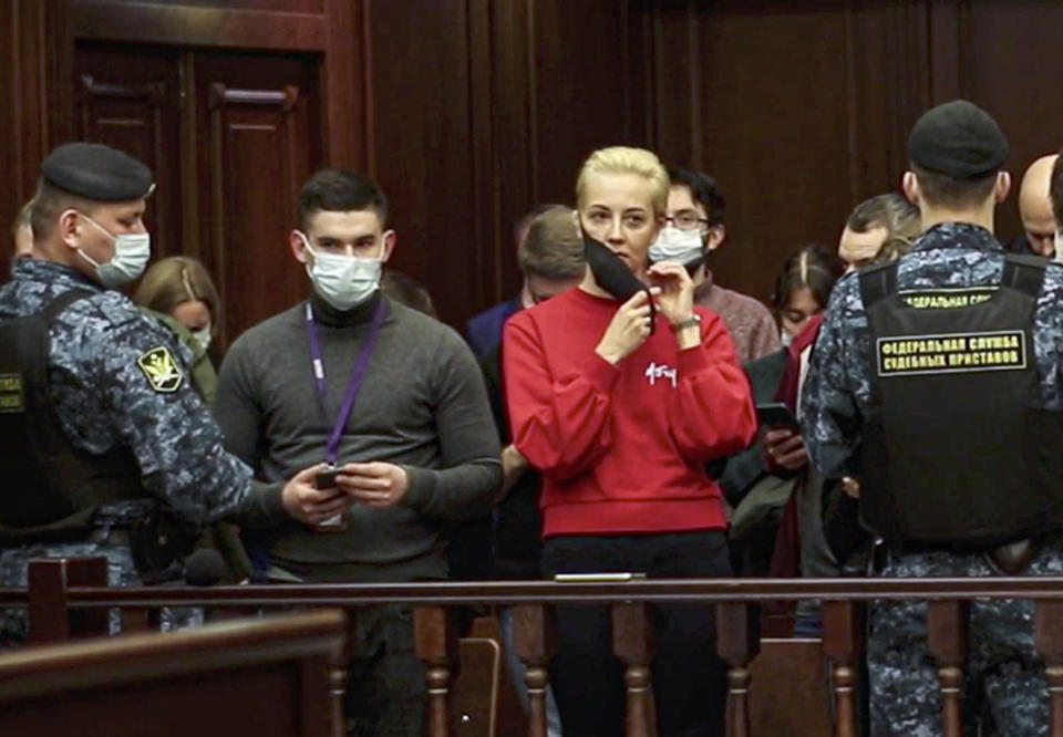 In this handout photo taken from a footage provided by Moscow City Court, the wife of Russian opposition leader Alexei Navalny, Yulia, in red, reacts attending a hearing to a motion from the Russian prison service to convert the suspended sentence of Navalny from the 2014 criminal conviction into a real prison term, in the Moscow City Court in Moscow, Russia, Tuesday, Feb. 2, 2021. A Moscow court has ordered Russian opposition leader Alexei Navalny to prison for more than 2 1/2 years for violating the terms of his probation while he was recuperating in Germany from nerve-agent poisoning. Navalny, who is the most prominent critic of President Vladimir Putin, had earlier denounced the proceedings as a vain attempt by the Kremlin to scare millions of Russians into submission. (Moscow City Court via AP)