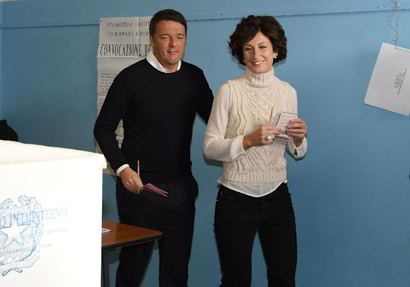 Italy's Prime Minister Matteo Renzi (L) and his wife Agnese Landini vote for a referendum on constitutional reforms, on December 4, 2016 at a polling station in Florence
