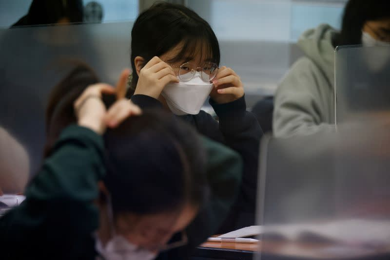 A student adjust her mask ahead of the annual college entrance examinations amid the coronavirus disease (COVID-19) pandemic at an exam hall in Seoul