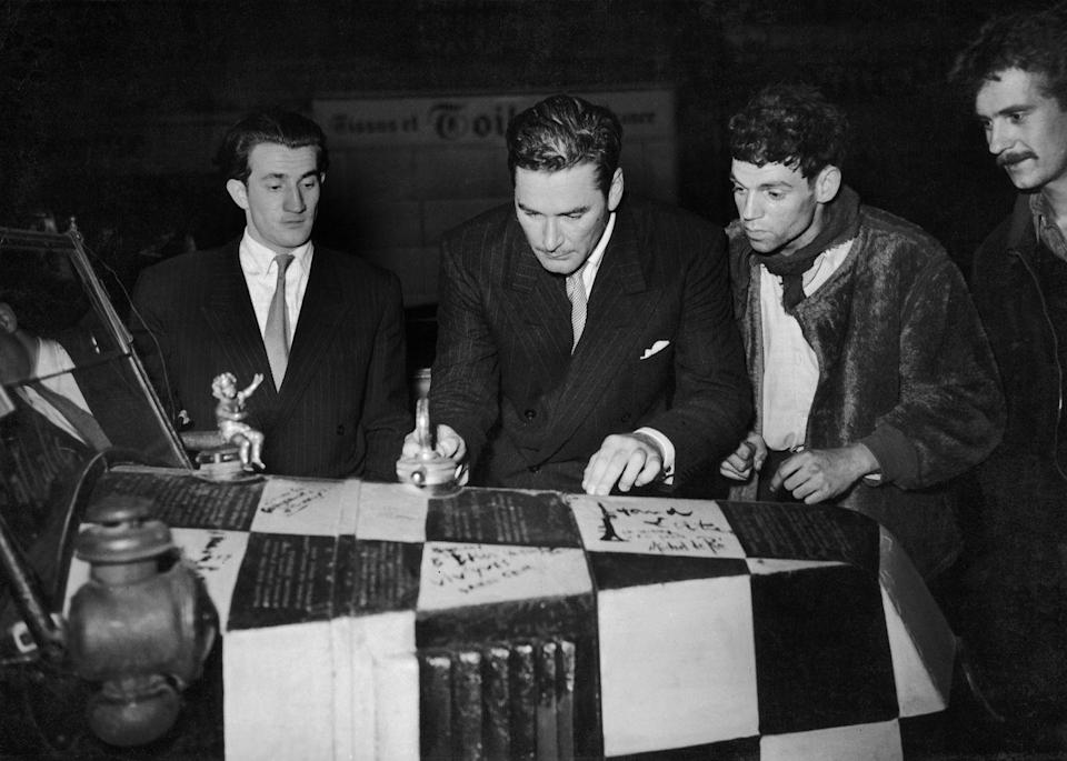 <p>The Old Hollywood actor signs a car hood at Club Du Vieux Colombier in Paris.</p>