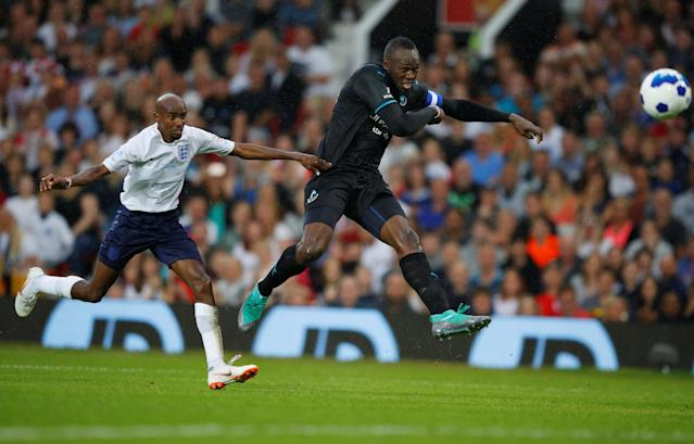 Soccer Football - Soccer Aid 2018 - England v Soccer Aid World XI - Old Trafford, Manchester, Britain - June 10, 2018 World XI's Usain Bolt in action with England's Mo Farah REUTERS/Phil Noble