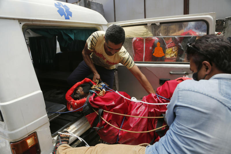 Hospital officials unload a dead body of an Indian mountaineer after the same was brought to Teaching hospital in Kathmandu, Nepal, Sunday, May 19, 2019. Two mountaineers died on Nepal's famous Himalayan peaks, while another two climbers were missing, officials said Friday. (AP Photo/Niranjan Shrestha)