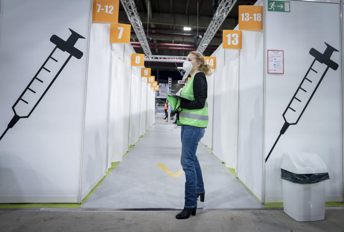 A volunteer stands inside the new open Erika-Hess-Eisstadion vaccine center in Berlin, Germany, Thursday, Jan. 14, 2021. (Kay Nietfeld/Pool vis AP)